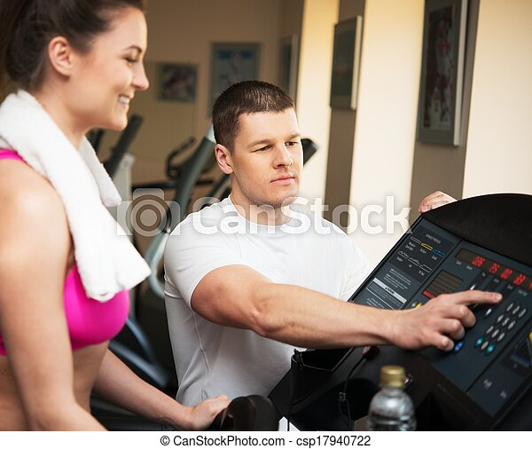 Trainer explains to a young woman how to use treadmill in fitness club - csp17940722