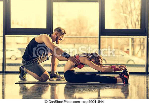 trainer, gebaard, vrouw stretching, jonge, portie, het glimlachen, zijaanzicht - csp49041844