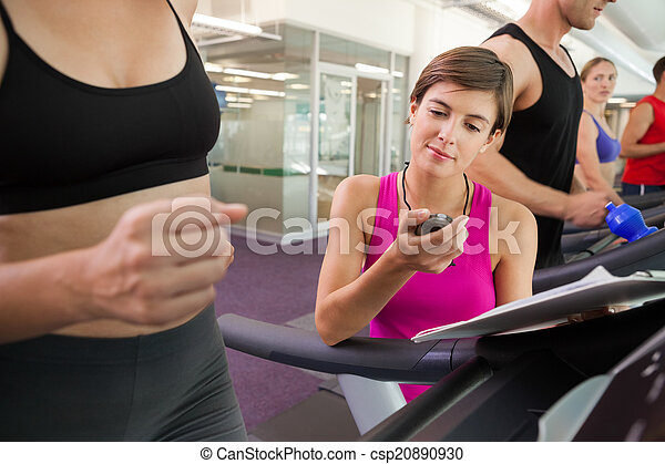 9d5d1c74c61 Trainer timing her client on the treadmill - csp20890930