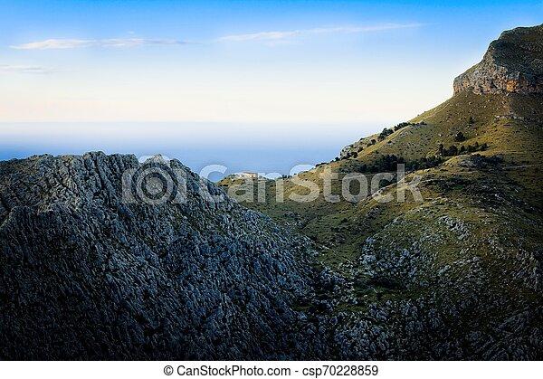 Tramuntana near Sa Calobra, lone house in the mountains at sunset, rocks, green pastures, mediterranean sea, blue sky, Mallorca, Spain. - csp70228859