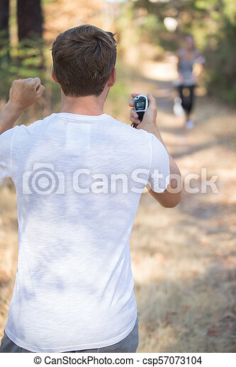 Traniner anxiously awaiting runner with stopwatch - csp57073104