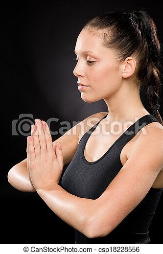 Tranquil woman performing yoga with eyes closed - csp18228556