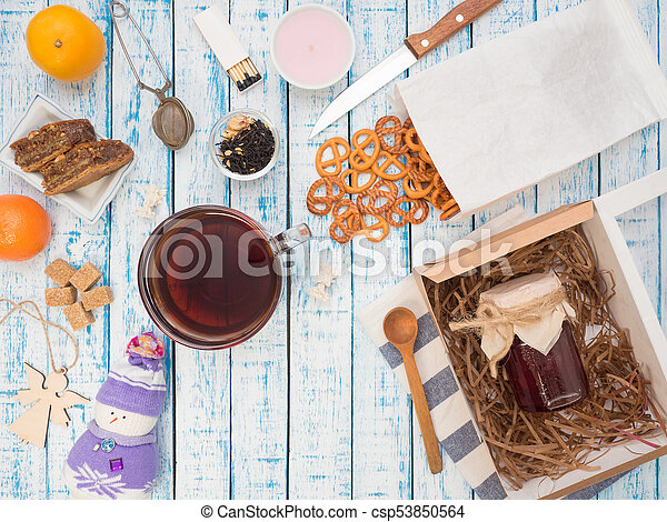 Transparent cup of black tea, cookies and lemon on a wooden table - csp53850564