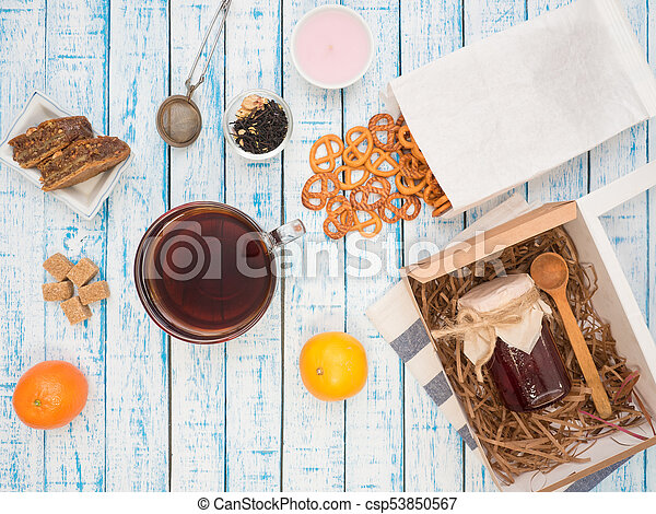 Transparent cup of black tea, cookies and lemon on a wooden table - csp53850567