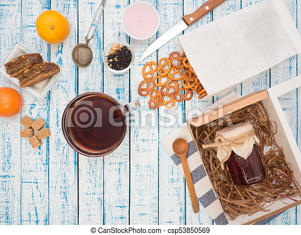 Transparent cup of black tea, cookies and lemon on a wooden table - csp53850569