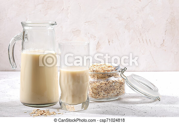 Transparent decanter and glass of oat milk and jar with oat flakes on white background. - csp71024818