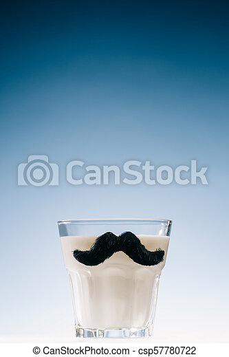 Transparent glass with mustaches filled with milk isolated on blue background - csp57780722