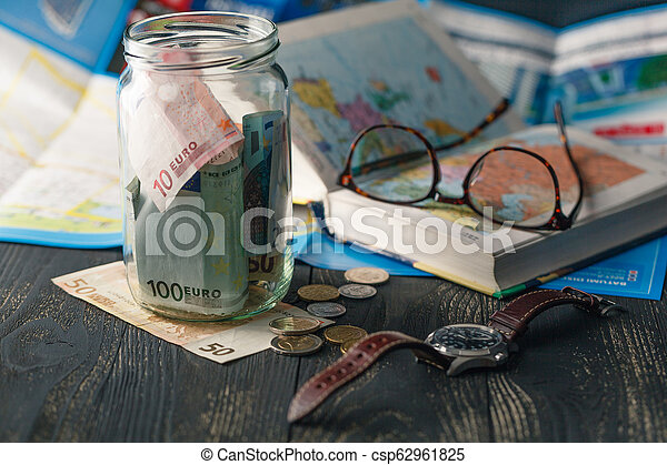 Travel budget - vacation money savings in a glass jar on world map - csp62961825