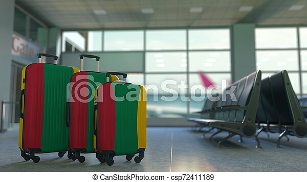 Travel suitcases with flag of Lithuania. Lithuanian tourism conceptual 3D rendering - csp72411189
