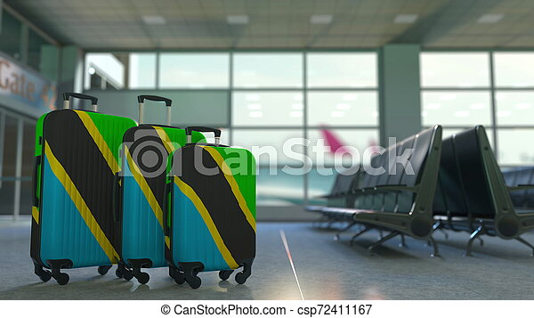 Travel suitcases with flag of Tanzania. Tanzanian tourism conceptual 3D rendering - csp72411167