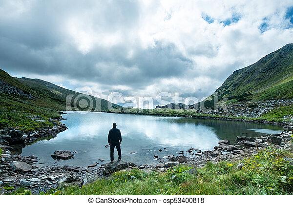 Traveler on the shore of a mountain lake - csp53400818