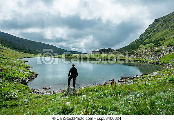 Traveler on the shore of a mountain lake - csp53400824