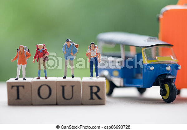 Traveler with backpack standing on wooden word TOUR with nature background - csp66690728