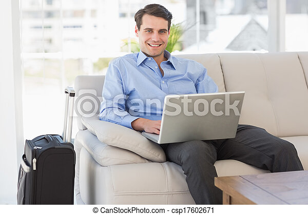 Traveling businessman using laptop sitting on the couch smiling - csp17602671