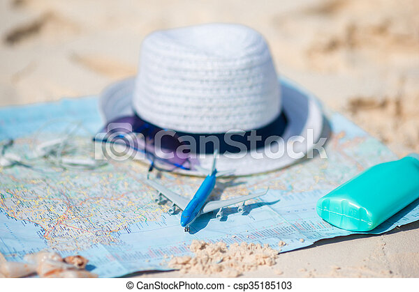 Traveling concept. Hat, suncream, sunglasses on a map of the world. - csp35185103
