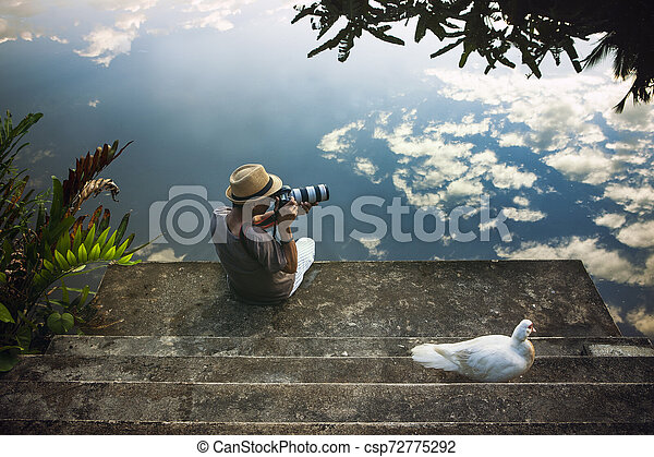 traveling man taking a photograph at old pier against beautiful blue sky reflection on water floor - csp72775292