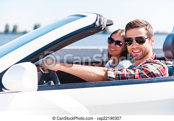Traveling with comfort. Happy young couple enjoying road trip in their white convertible while both looking at camera and smiling - csp22190307
