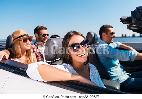 Traveling with fun. Group of young happy people enjoying road trip in their white convertible - csp22190627
