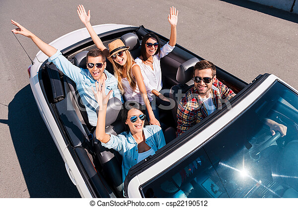 Traveling with fun. Top view of young happy people enjoying road trip in their white convertible and raising their arms - csp22190512