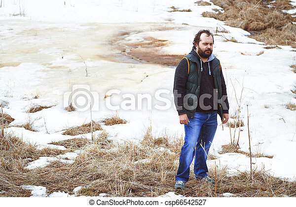 Traveller standing in the field with snow - csp66542527