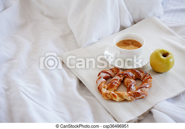 Tray with breakfast on a bed. Sweet pretzel, Cup of coffee and Apple - csp36496951
