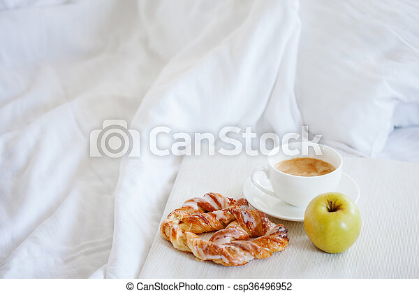Tray with breakfast on a bed. Sweet pretzel, Cup of coffee and Apple - csp36496952
