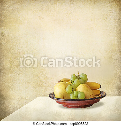 Tray with fruits on a table against a grunge wall - csp8905523