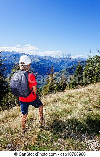 Jovencito parado a lo largo de una montaña usando un teléfono inteligente - csp10700966