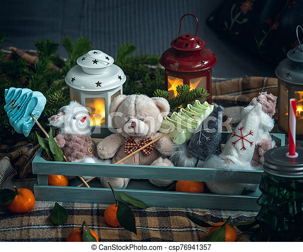 Treat and gift on a festive evening with meringue cookies in the form of Christmas trees and tangerines. Cute toys in a wooden box - csp76941357