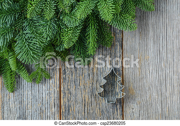Tree branch on rustic wooden background with cookie cutter orna - csp23680205