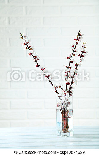 Tree Branches With Flowers In Vase On Blue Wooden Table