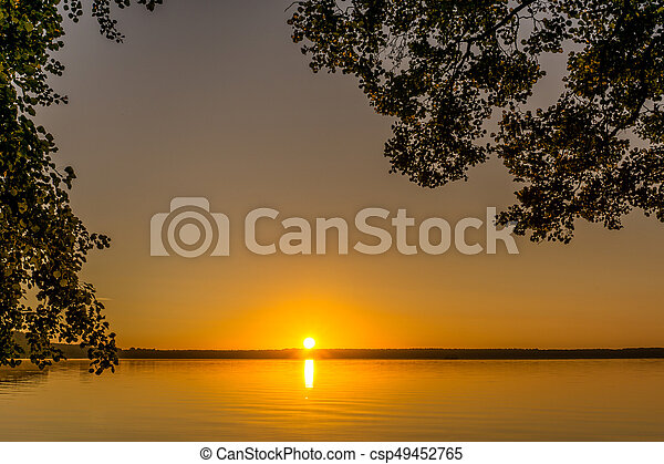 Trees at sunrise on a small lake - csp49452765