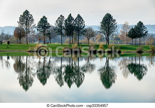trees reflecting in the lake - csp33354957
