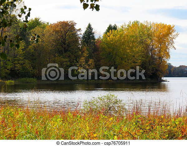 Trees with the color of Fall by the river in Laval, Quebec - csp76705911