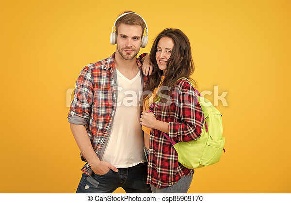 trendy dressed students. back to school. People lifestyle concept. university student dating. Two cheerful students. study together. woman carry backpack. man listen music in headset. feeling carefree - csp85909170