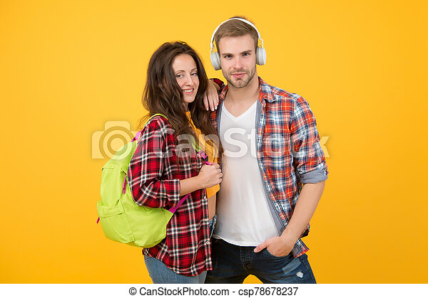trendy dressed students. back to school. People lifestyle concept. university student dating. Two cheerful students. study together. woman carry backpack. man listen music in headset. feeling carefree - csp78678237