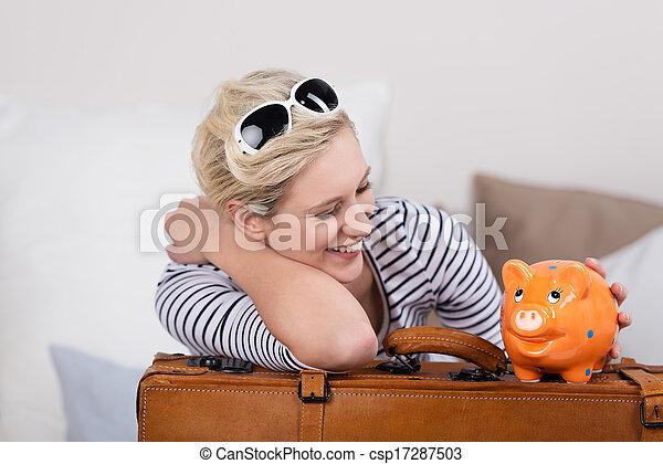 Trendy traveler with a piggy bank - csp17287503