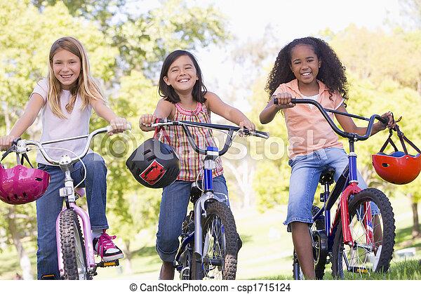 Tres jóvenes amigas al aire libre en bicicleta sonriendo - csp1715124