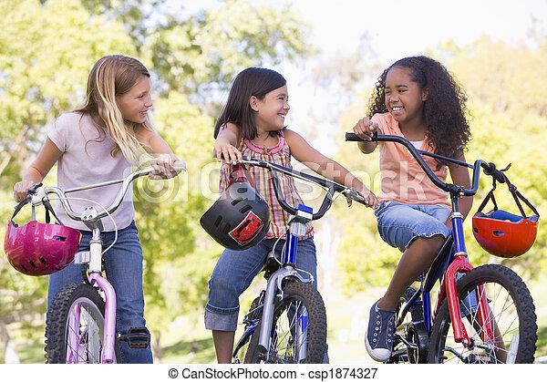 Tres jóvenes amigas al aire libre en bicicleta sonriendo - csp1874327