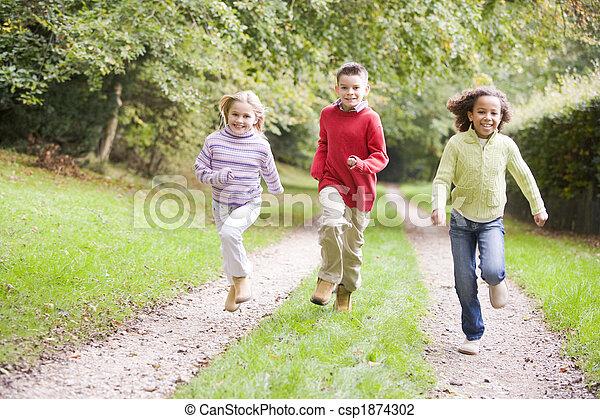 Tres jóvenes amigos corriendo por un camino al aire libre sonriendo - csp1874302