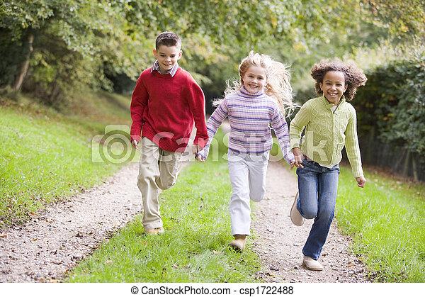 Tres jóvenes amigos corriendo por un camino al aire libre sonriendo - csp1722488