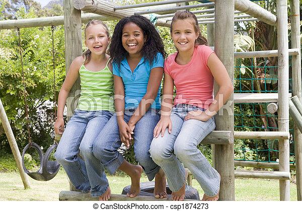 Tres jóvenes amigas en un patio de juegos sonriendo - csp1874273