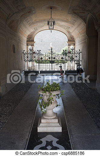 Treviglio (Bergamo, Lombardy, Italy), entrance of historic palace with plants and two bicycles - csp6885186
