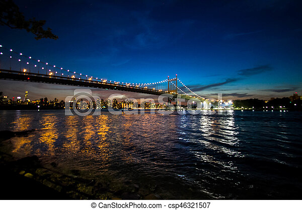 Triborough bridge over the reflective river and buildings at night, New York - csp46321507