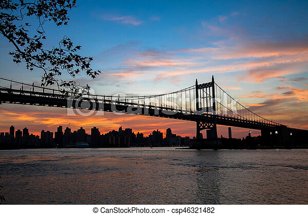 Triborough bridge over the river and buildings in silhouette and sunset sky - csp46321482