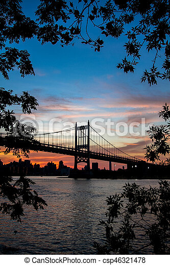 Triborough bridge over the river with branches in silhouette, New York - csp46321478