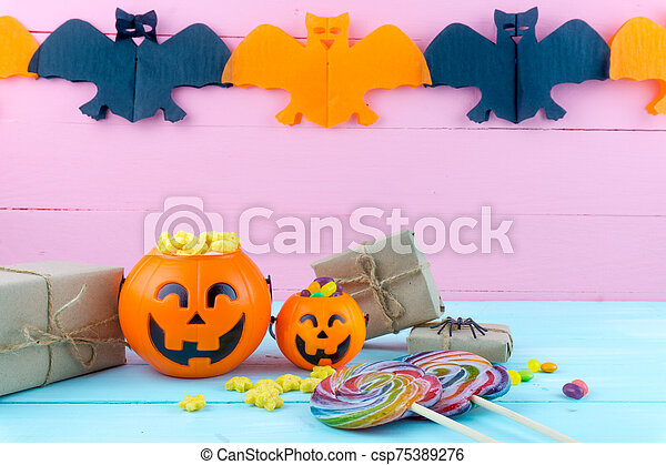 Trick or Treat - Halloween jack o' lantern, candy and rainbow lollipop on pink and blue wooden background with copy space for text. Flat lay, top view - csp75389276
