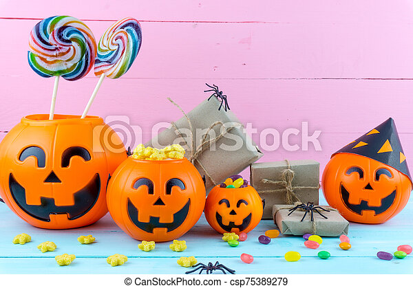 Trick or Treat - Halloween jack o' lantern, candy and rainbow lollipop on pink and blue wooden background with copy space for text. Flat lay, top view - csp75389279