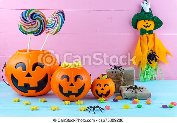 Trick or Treat - Halloween jack o' lantern, candy and rainbow lollipop on pink and blue wooden background with copy space for text. Flat lay, top view - csp75389286