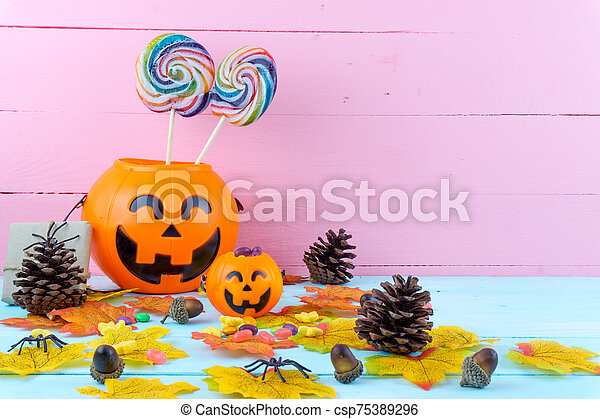 Trick or Treat - Halloween jack o' lantern, candy and rainbow lollipop on pink and blue wooden background with copy space for text. Flat lay, top view - csp75389296